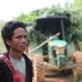 One of the village leaders stands in front of a confiscated palm oil company truck.